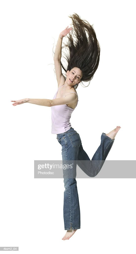 a young adult female in jeans and a pink shirt jumps up playfully in the air : Foto de stock
