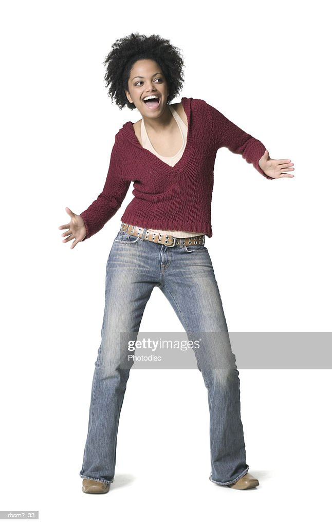 a young adult female in jeans and a red sweater dances around and smiles : Stockfoto