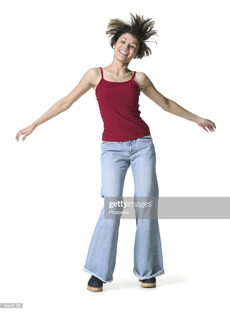 a young adult female in jeans and a red tank top dances and tosses her head around : Foto de stock