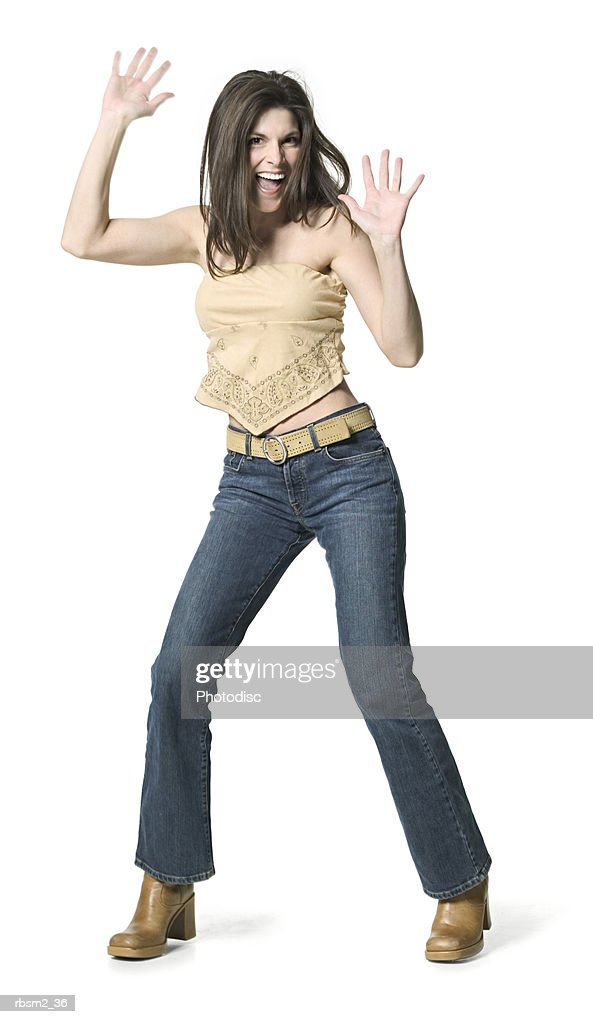 a young adult female in jeans and a tan shirt dances around and holds up her arms : Stockfoto