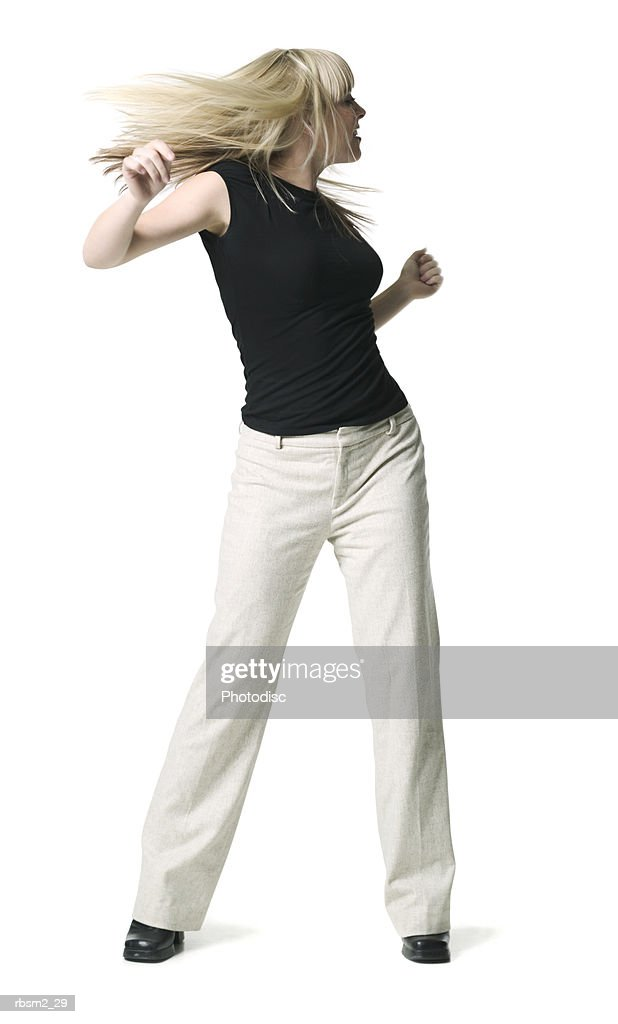 a young adult female in tan pants and a black shirt dances and tosses her hair around : Foto de stock