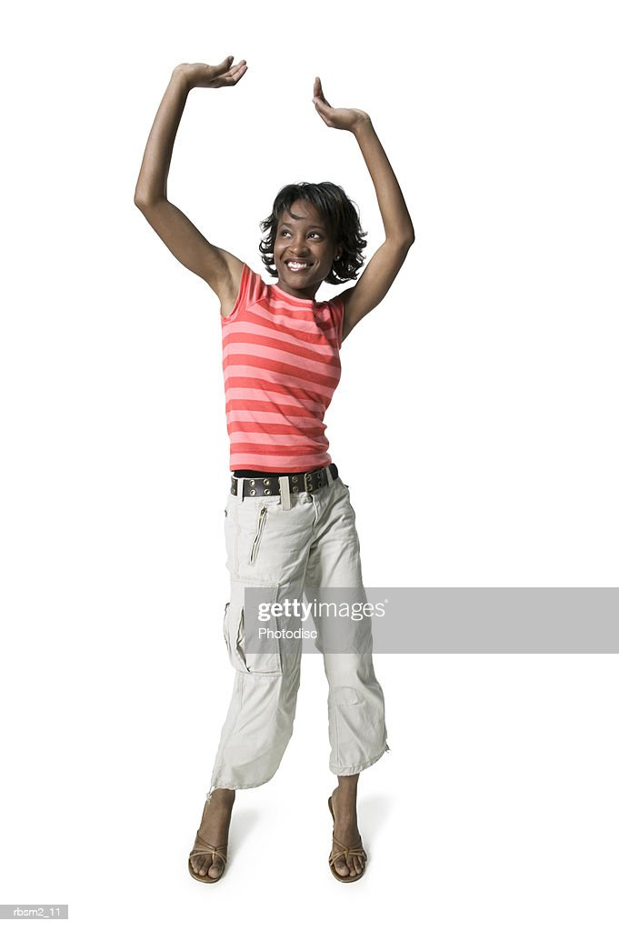 a young adult female in tan pants and a striped shirt puts up her arms and dances playfully : Foto de stock