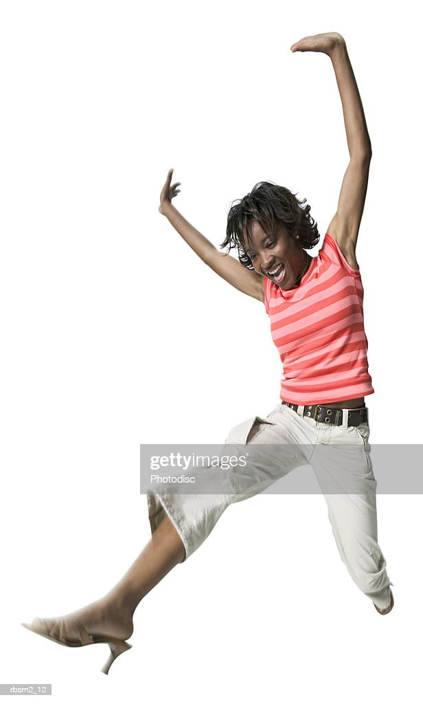 a young adult female in tan pants and a striped shirt puts up her arms and jumps through the air : Foto de stock