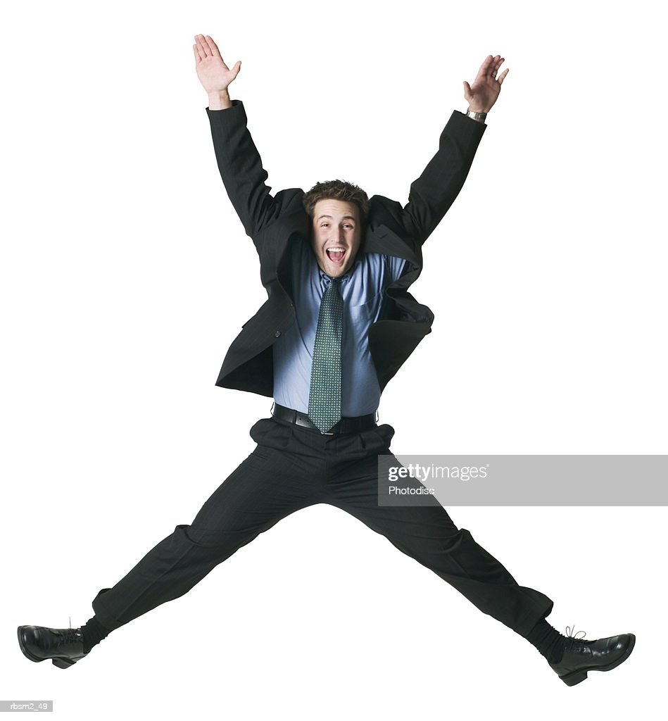 a young adult male in a business suit jumps up wildly into the air : Foto de stock