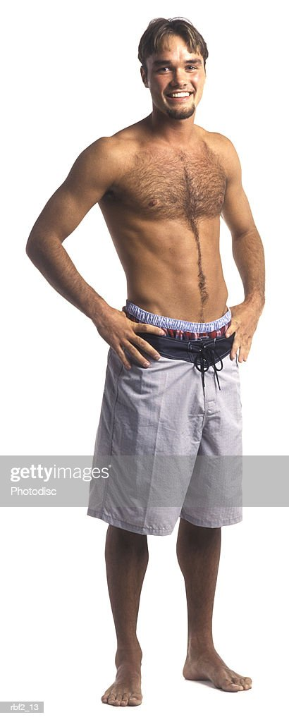 a young adult male in a grey bathing suit puts his hands on his hips and smiles : Stockfoto