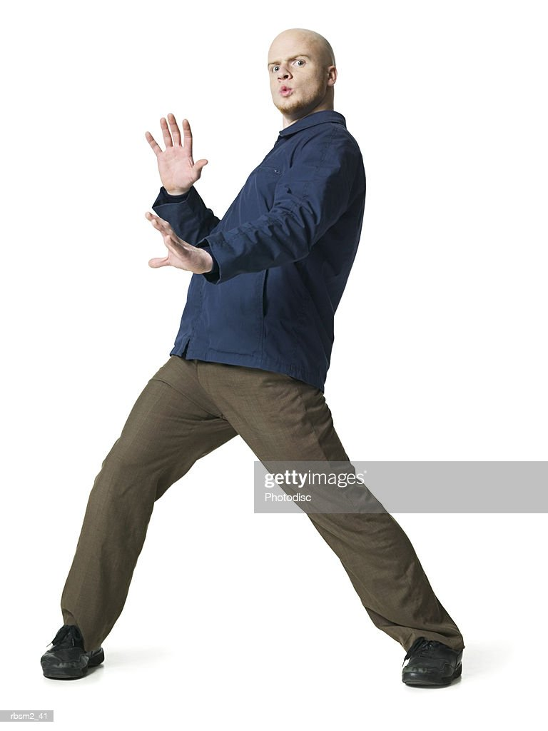 a young adult male in brown pants and a blue jacket dances around playfully : Foto de stock