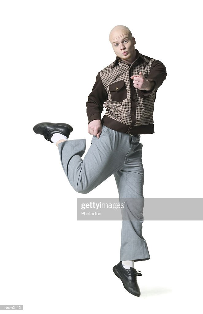 a young adult male in grey pants and a brown shirt jumps up and around playfully : Foto de stock