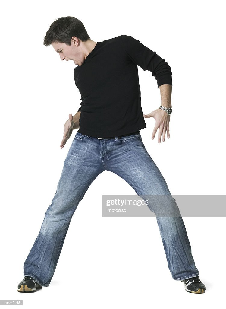a young adult male in jeans and a black shirt as he dances around : Foto de stock