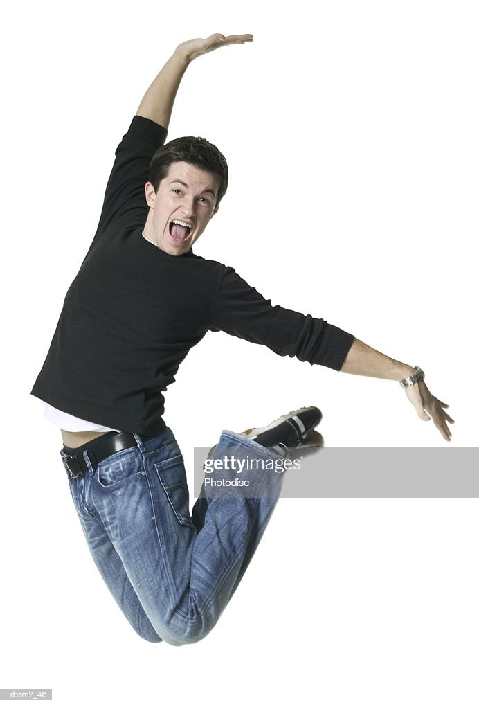 a young adult male in jeans and a black shirt jumps up playfully through the air : Foto de stock