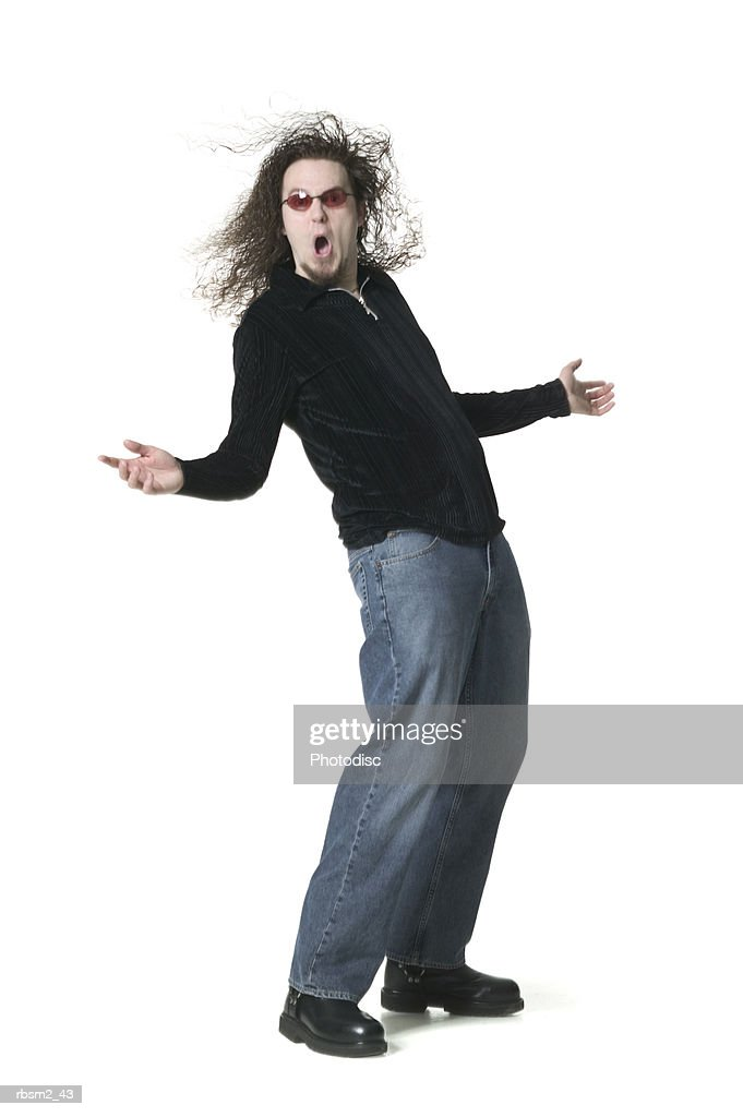 a young adult male in jeans and a black shirt leans back and spreads out his arms : Stockfoto
