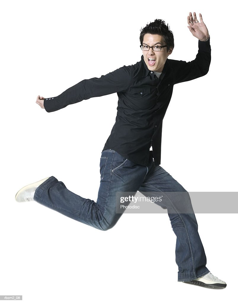 a young adult male in jeans and a black shirt runs and jumps playfully through the air : Foto de stock