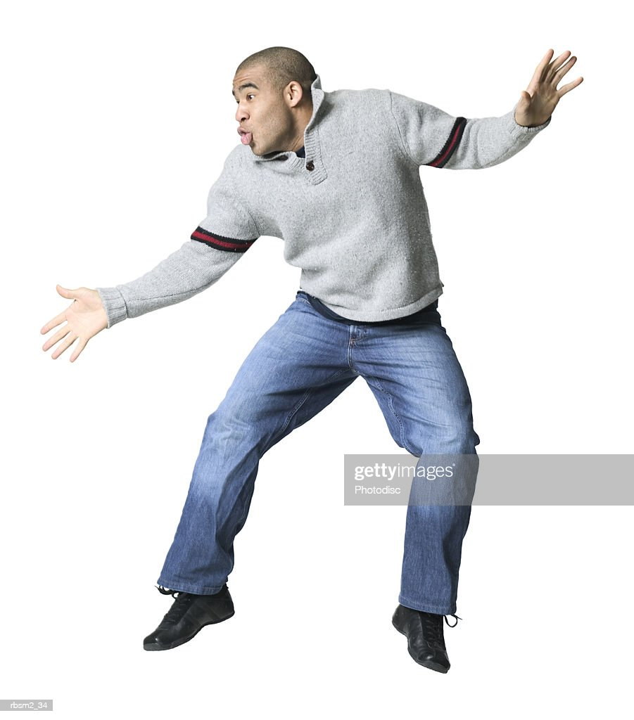 a young adult male in jeans and a grey shirt sweater as he does a silly dance : Foto de stock