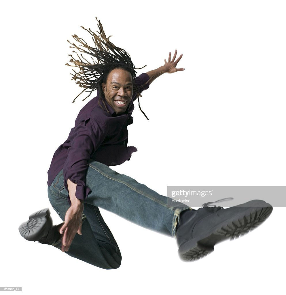 a young adult male in jeans and a purple shirt  jumps and kicks through the air : Foto de stock