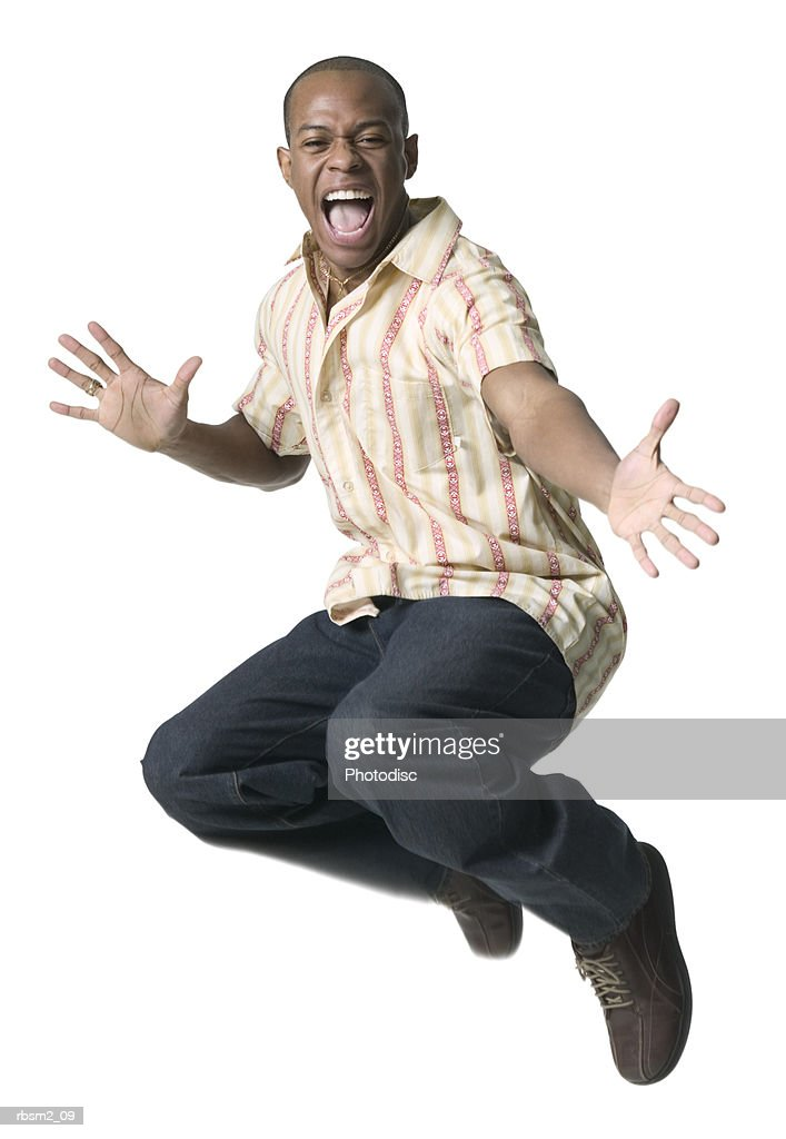 a young adult male in jeans and a striped shirt jumps up playfully into the air : Foto de stock