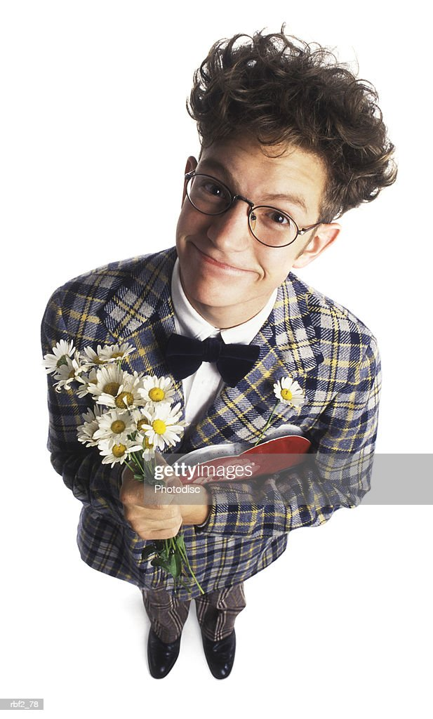 a young adult male nerd in a plaid suit with flowers and chocolates smiles up at the camera : Foto de stock