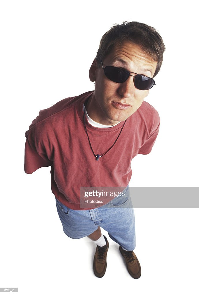 a young adult man in a red shirt and sunglasses glances up at the camera : Stockfoto