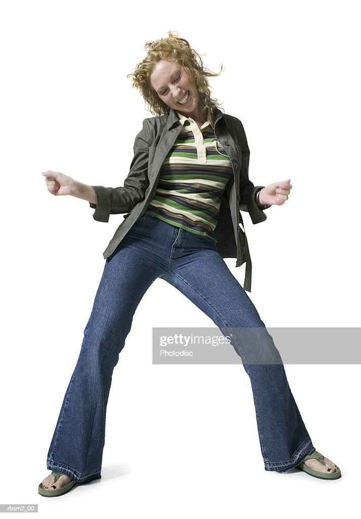 a young adult woman in jeans and a green jacket dances playfully : Foto de stock