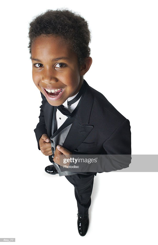 a young african american boy dressed in a tuxedo smiles up into the camera : Foto de stock