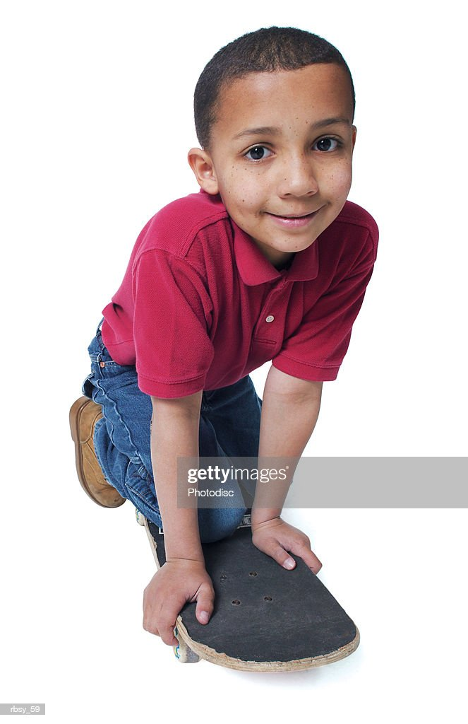 a young african american boy in jeans and a red shirt leans over a skateboard and smiles : Foto de stock