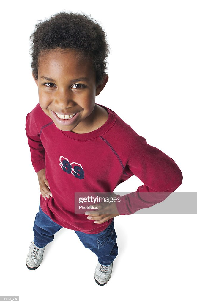 a young african american boy in jeans and a red shirt puts his hands on his hips and smiles up into the camera : Foto de stock