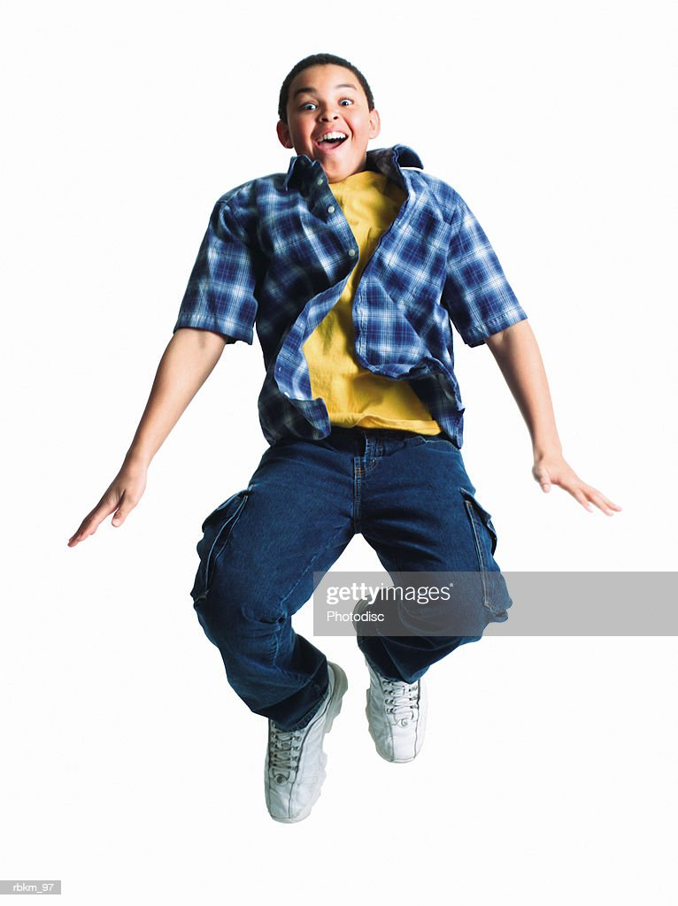 a young african american boy jumps straight up into the air and makes a surprised expression : Stockfoto