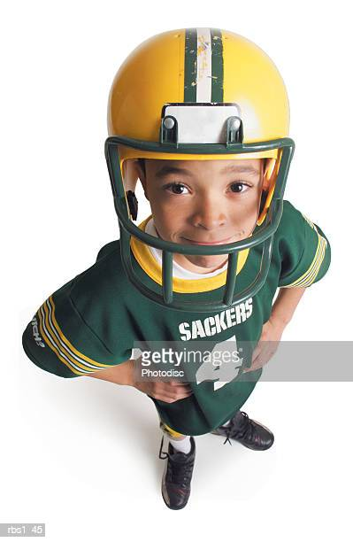 a young african american boy wearing a green and yellow footfall uniform is smiling as he looks up at the camera - american football strip stock pictures, royalty-free photos & images