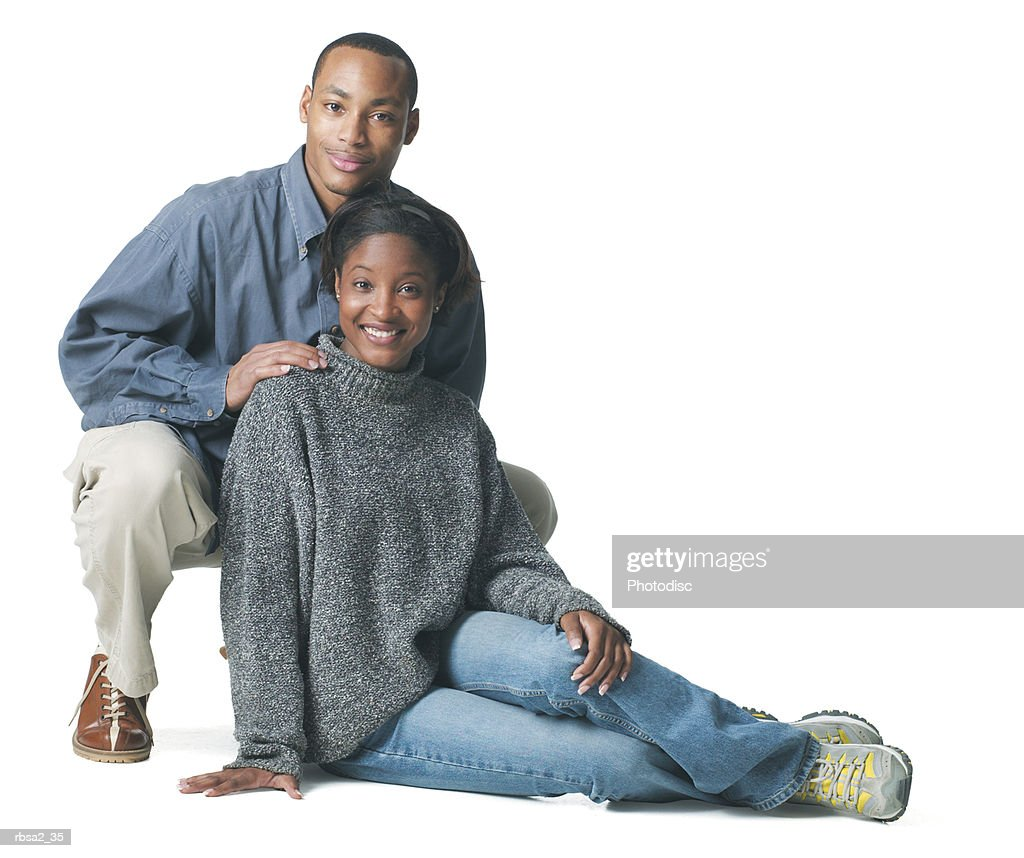 a young african american couple sits down and smiles at the camera : Foto de stock