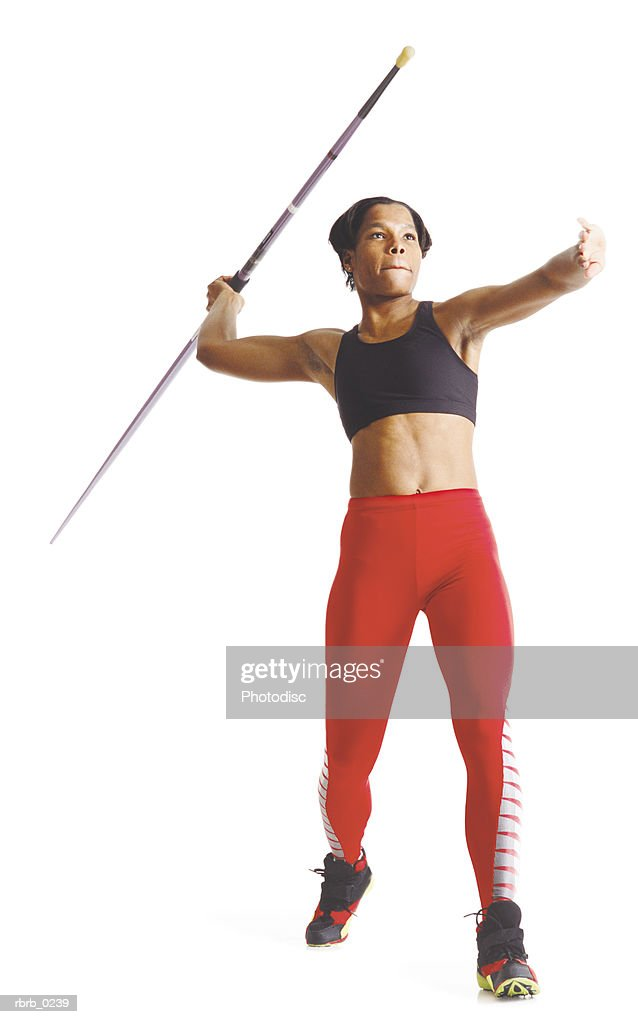 a young african american female athlete in red pants and a black sports bra pulls her arm back to release a javelin : Stockfoto