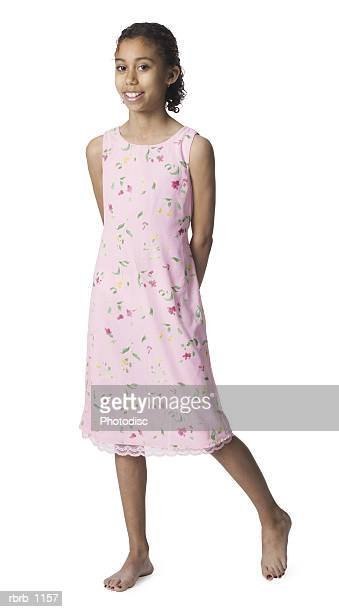 a young african american female child in a pink dress and and bare feet smiles happily