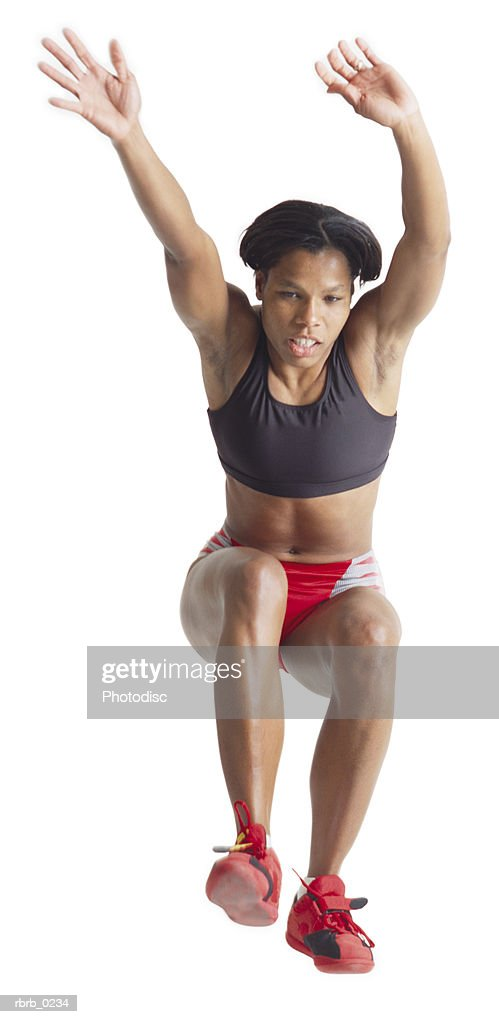a young african american female track and field participant flies through the air during the long jump : Stockfoto