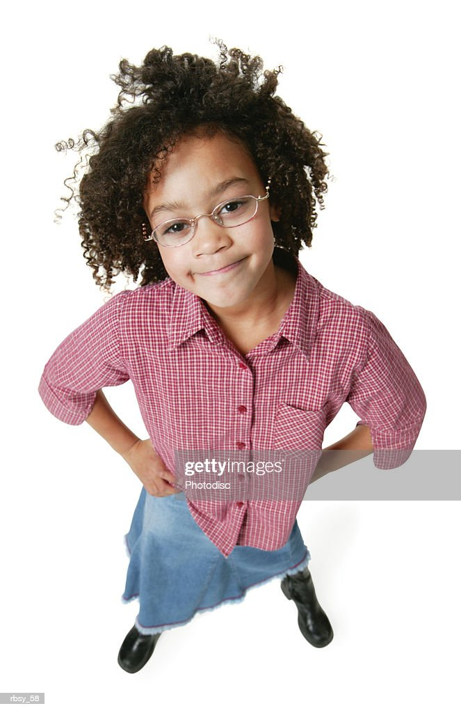 a young african american girl in a jeans skirt and a red shirt puts her hands on her hips and smiles up at the camera : Foto de stock