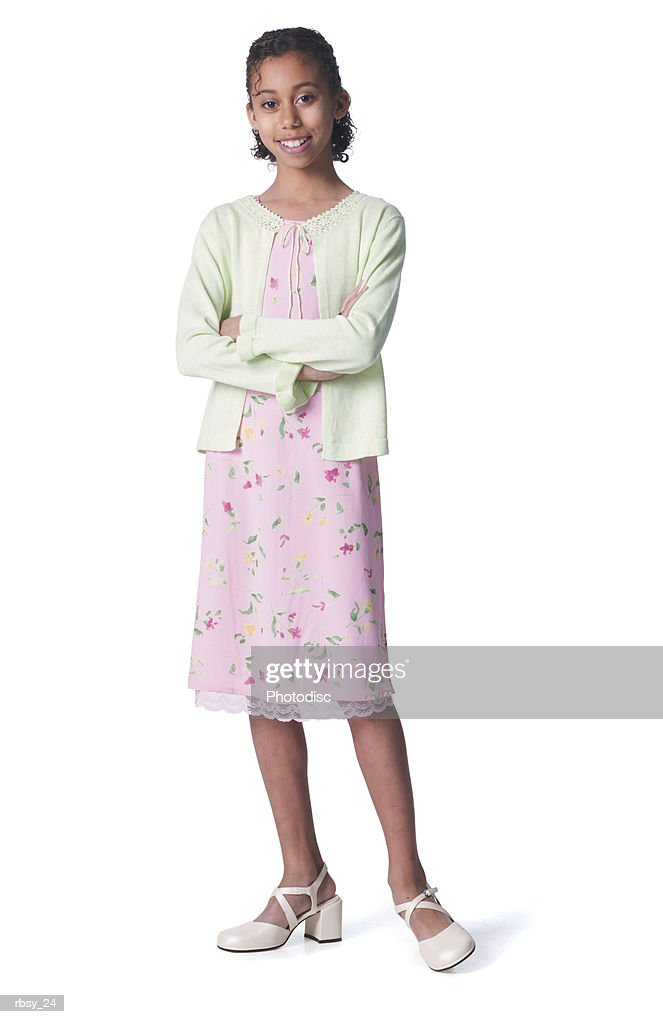 a young african american girl in a pink floral skirt and green sweater folds her arms and smiles : Foto de stock