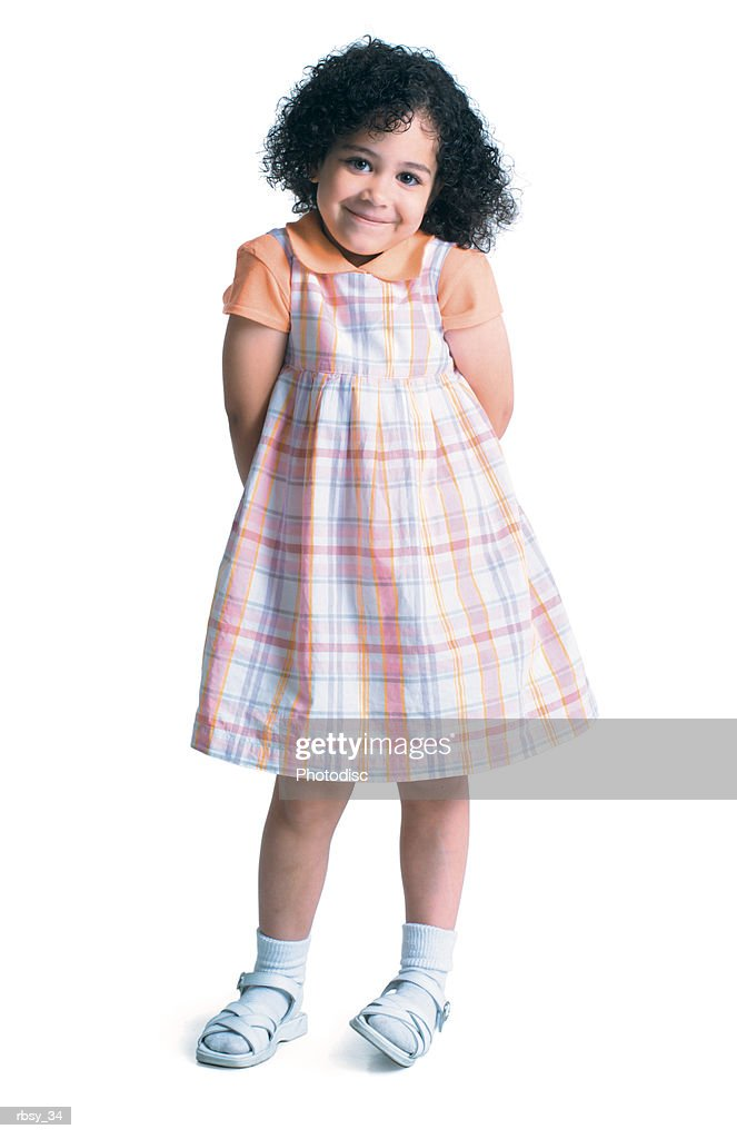 a young african american girl in a plaid dress as she puts her hand behind her back and smiles : Foto de stock