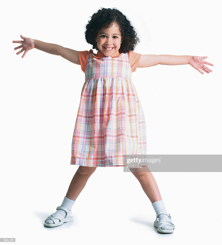 a young african american girl in a plaid dress stretches out her arms and legs and smiles : Stockfoto
