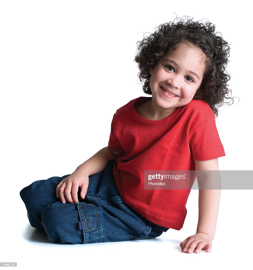a young african american girl in jeans and a red shirt sits down and smiles : Foto de stock