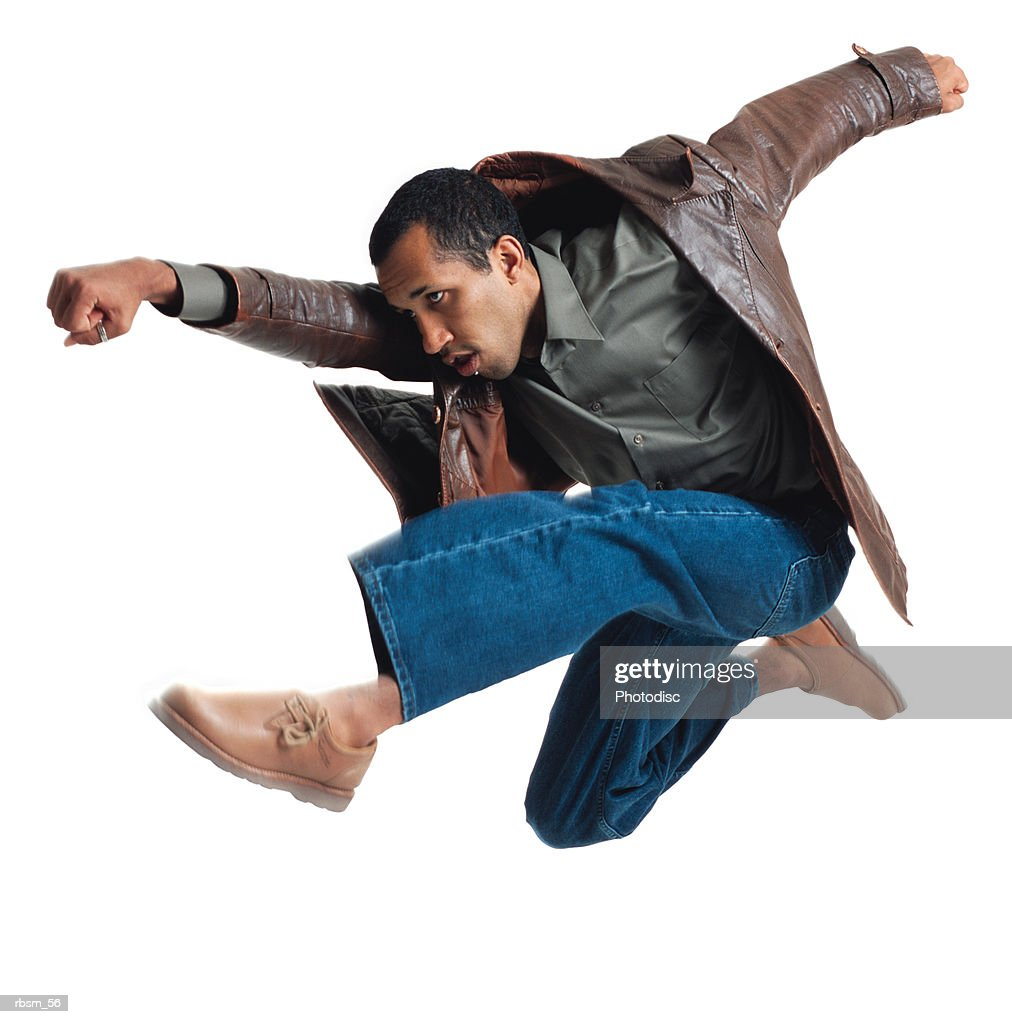 a young african american male dancer in jeans a green shirt and a leather jacket jumps up as if flying and throws a fist forward : Stockfoto