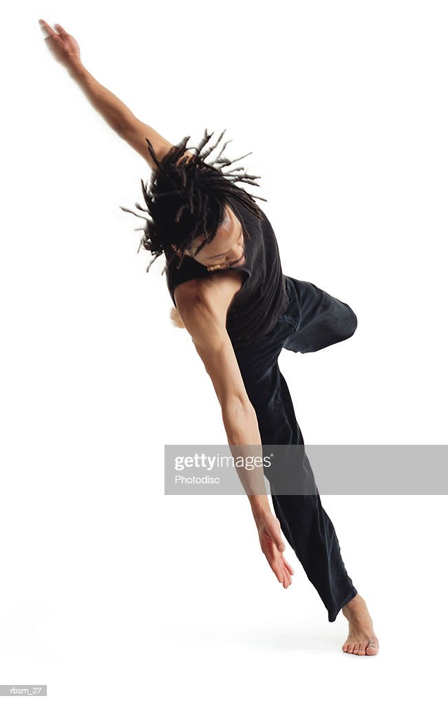 a young african american male modern dancer in black pants and a black tank top jumps up on one foot and spins : Foto de stock