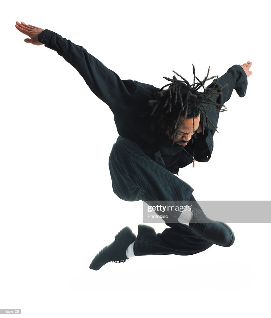 a young african american male modern dancer in black pants and shirt leaps up and flies through the air while outstretching his arms : Stockfoto