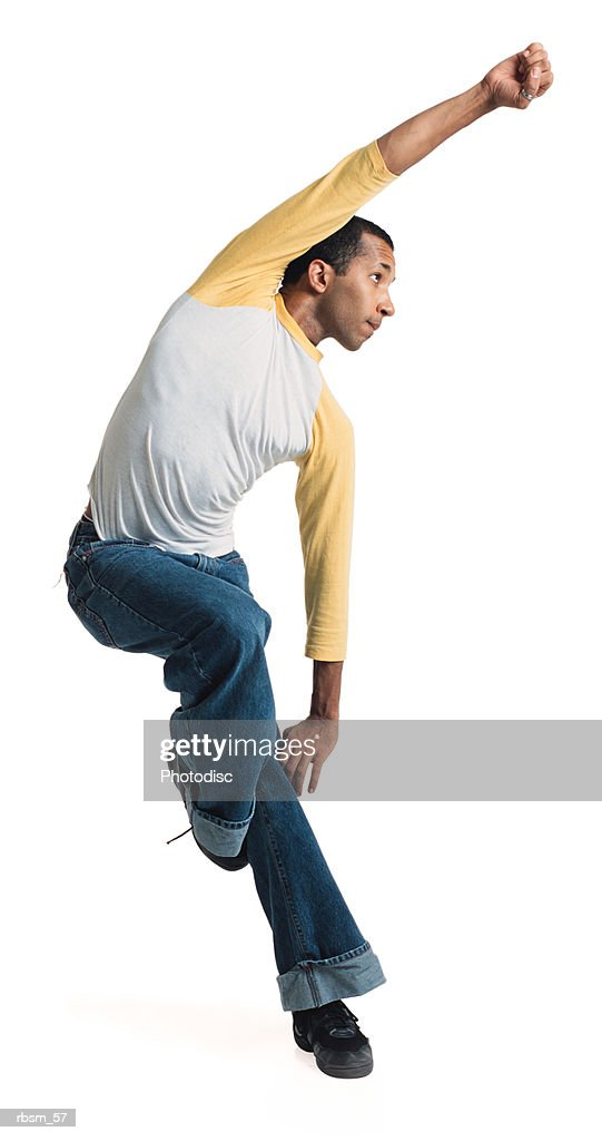 a young african american male modern dancer in jeans and a white and yellow baseball shirt balances on one leg and throws his fist into the air : Stockfoto