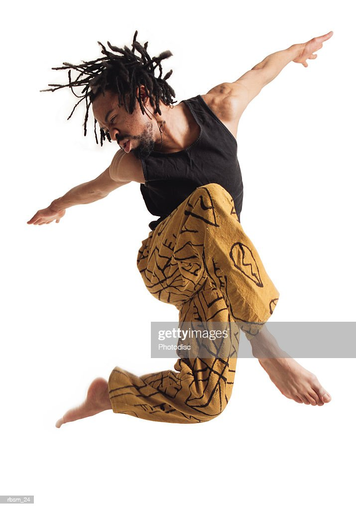 a young african american male modern dancer in yellow pants and a black tank top leaps into the air and spreads his arms apart : Foto de stock
