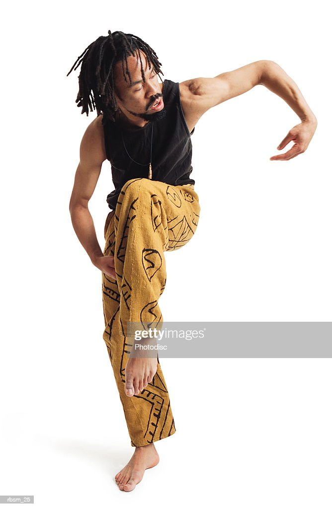 a young african american male modern dancer in yellow pants and a black tank top balances on one leg and curves his arm out : Foto de stock