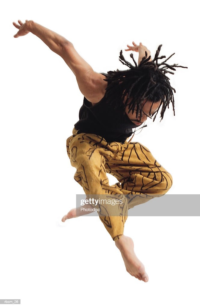 a young african american male modern dancer in yellow pants and a black tank top flies through the air downward as he throws his arms back : Foto de stock