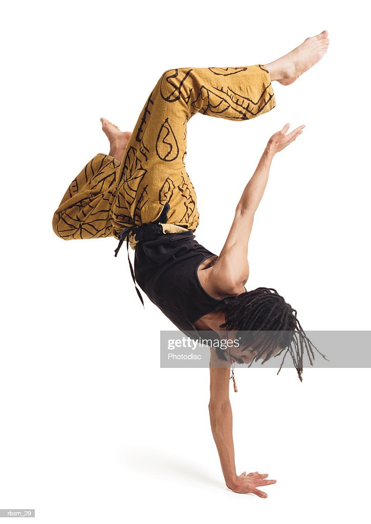 a young african american male modern dancer in yellow pants and a black tank top flips himself upside down with one arm and carefully balances : Foto de stock