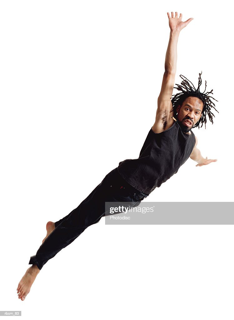 a young african american male modern dancer with dreadlocks dressed in black flies through the air and dives sideways : Foto de stock