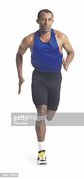 a young african american male runner in black shorts and a blue tank runs forward