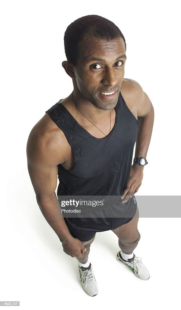 a young african american male runner wearing black shorts and tank top stands smiling looking up into the camera : Foto de stock