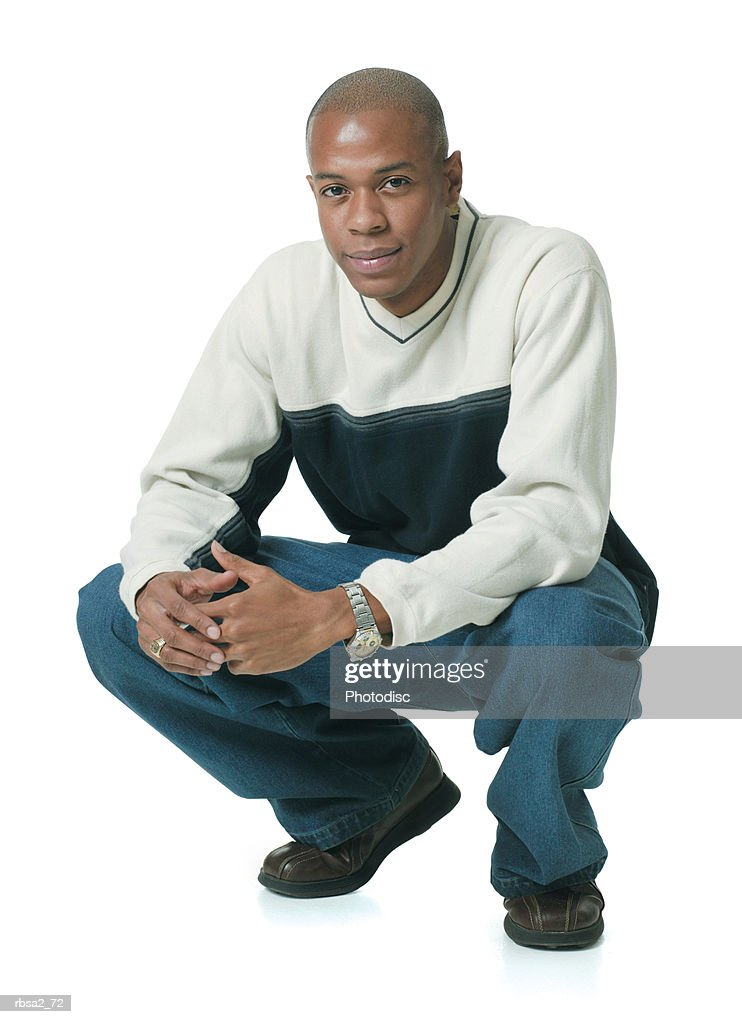 a young african american man in jeans and a blue and tan sweater crouches down and smiles slightly : Stockfoto