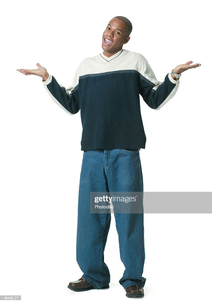 a young african american man in jeans and a tan and blue sweater undecidedly holds out his arms and shrugs his shoulders : Foto de stock