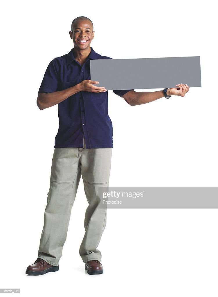 a young african american man in tan pants and a black shirt holds a blank sign up to his side with both hands : Stockfoto