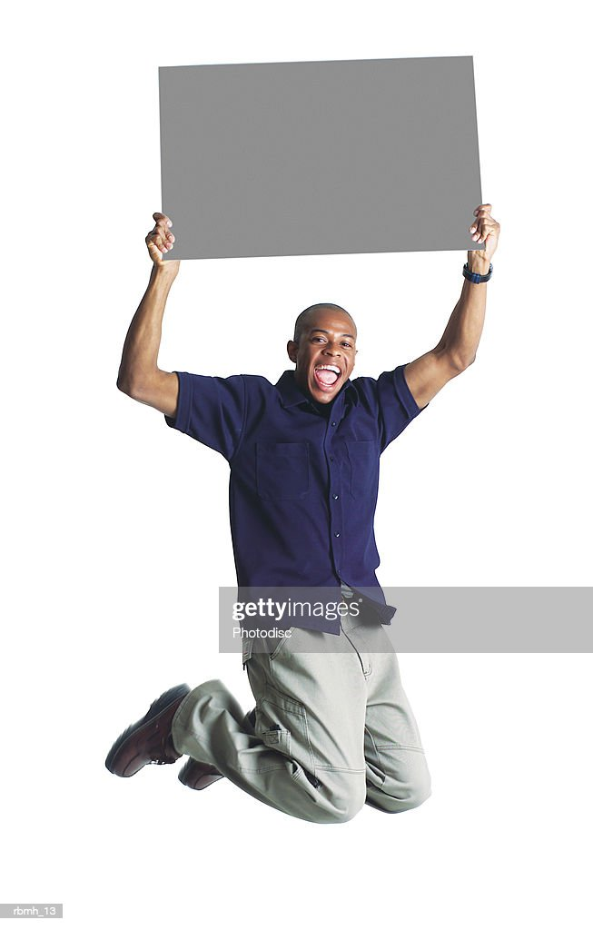 a young african american man in tan pants and a black shirt jumps up while holding a blank sign : Stockfoto